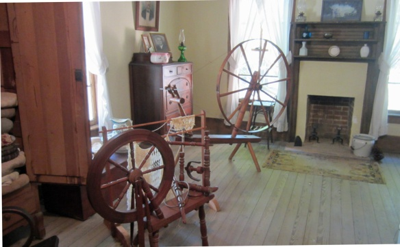 The spinning wheel in the foreground is for flax, the larger one is for wool.